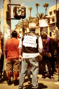 Black Lives Matter protester from behind, sign on back if they start shooting stand behind me Photo by Mandy Rosen