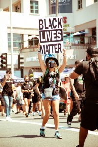 Woman in hat holding Black Lives Matter sign in front of Huntington Surf and Sport