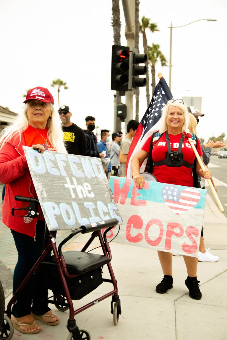 Two blonde women wearing red holding Defend the Police signs, anti-protesters, anti-BLM