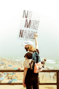 Young man on HB Pier with skateboard holing a sign No More Names