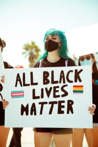 Blue haired girl, wearing a mask holding All Black Lives Matter sign