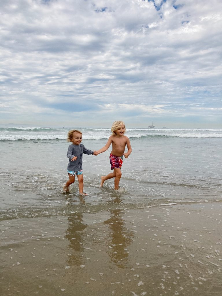 Two young brothers walking hand in hand in Huntington Beach